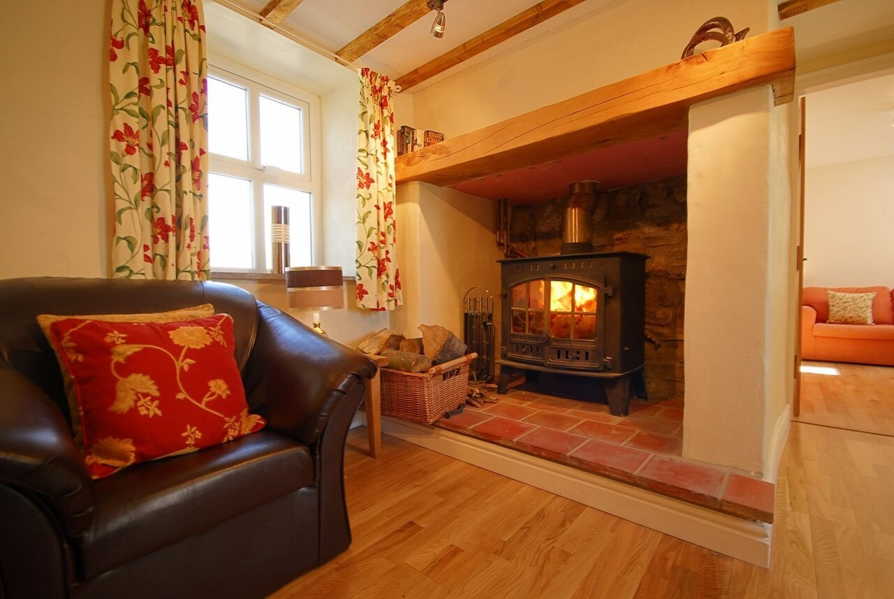 Cosy sitting room with log fire and comfy sofas